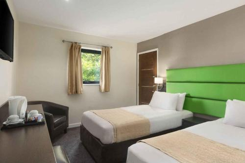 A bed or beds in a room at Ramada Birmingham Oldbury M5 J2