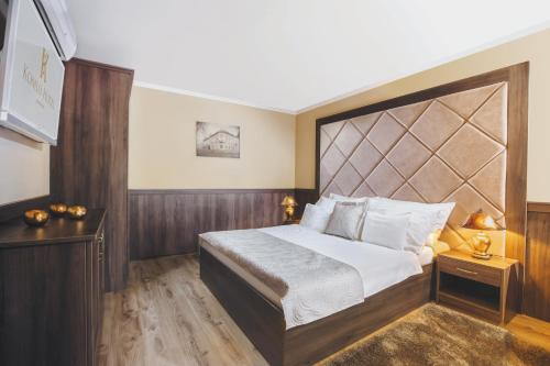 A bed or beds in a room at Komló Hotel Gyula