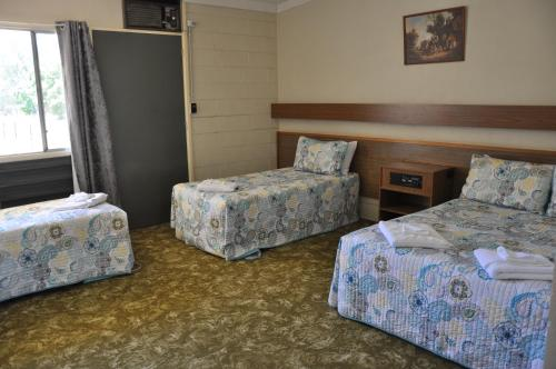 A bed or beds in a room at The King's Own Hotel Motel