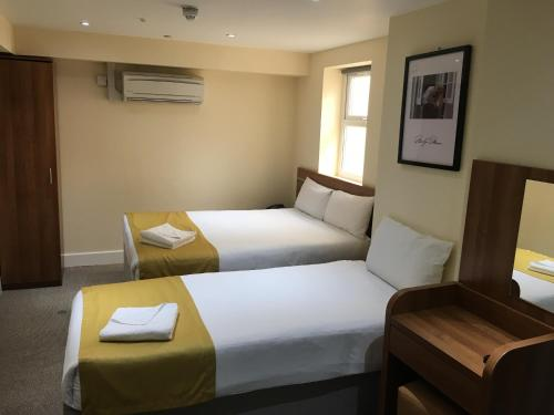 A bed or beds in a room at Park Avenue Inn Craven London Hyde Park