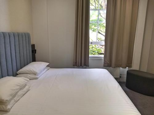 A bed or beds in a room at Garden Court Hotel