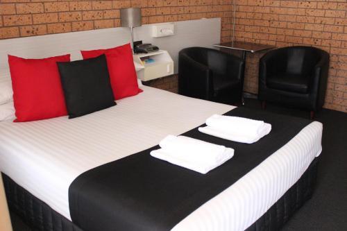 A bed or beds in a room at Golden Harvest Motor Inn Moree