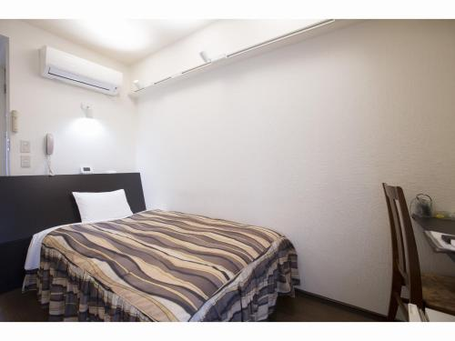 A bed or beds in a room at Hotel Tetora Tsurumi