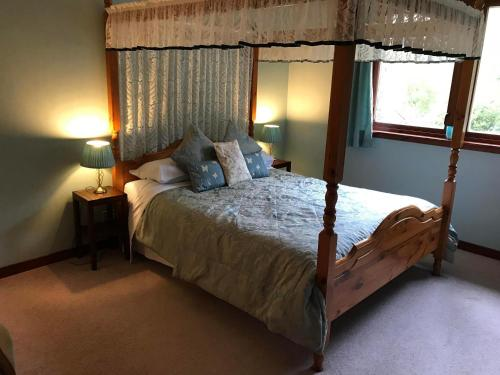 A bed or beds in a room at Drumbuie Farm B&B
