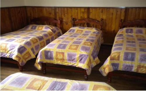 A bed or beds in a room at Hostal Valle Hermoso II