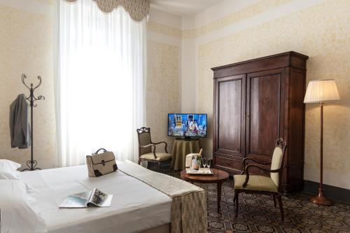 A television and/or entertainment center at BW Premier Collection Grand Hotel Royal