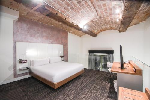 A bed or beds in a room at Petit Palace Boqueria Garden