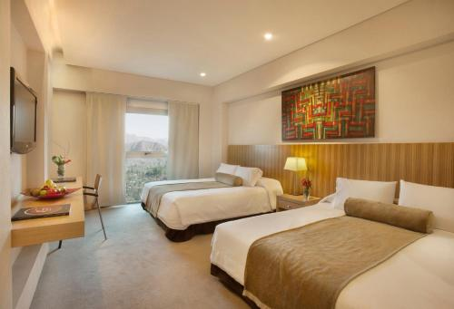 A bed or beds in a room at Mod Hotels Mendoza