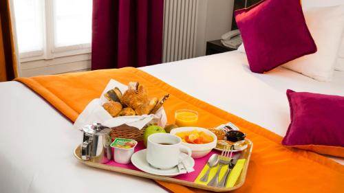 A bed or beds in a room at Hôtel Du Plat d'Etain