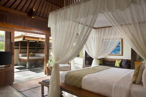 A bed or beds in a room at Ubud Village Hotel