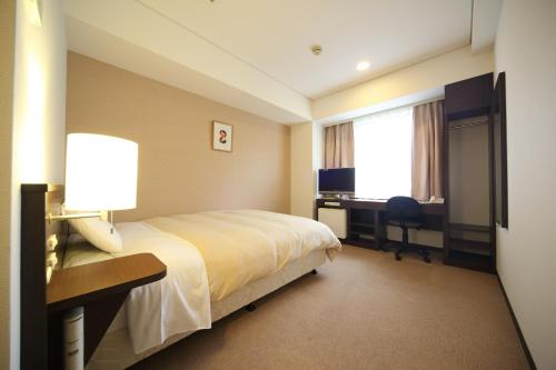 A bed or beds in a room at Hotel Park Side Hiroshima Peace Park