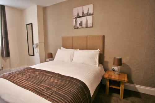A bed or beds in a room at New County Hotel by RoomsBooked