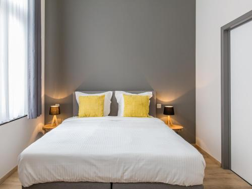 A bed or beds in a room at Urban Suites Brussels Schuman