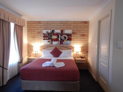 A bed or beds in a room at Cotswold Motor Inn
