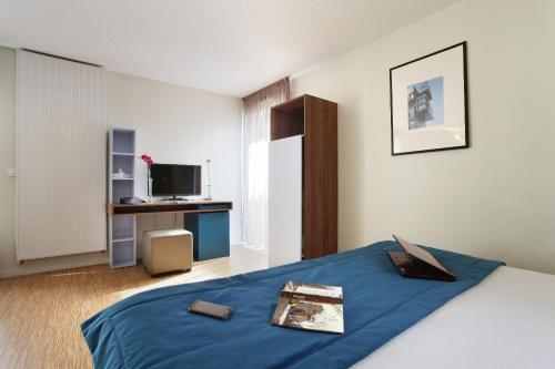 A bed or beds in a room at Odalys City Lyon Confluence