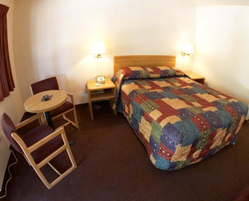 A bed or beds in a room at Rosedale Inn Bakersfield