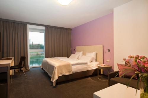 A bed or beds in a room at Hotel City Maribor