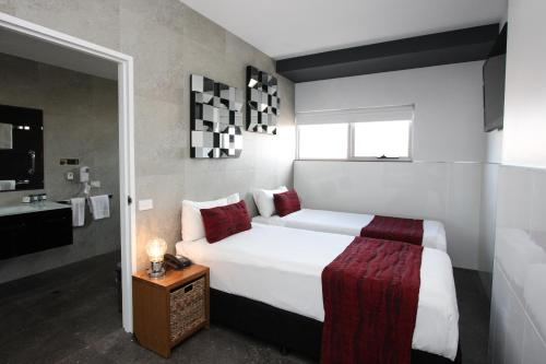 A bed or beds in a room at Honeysuckle Executive Apartments