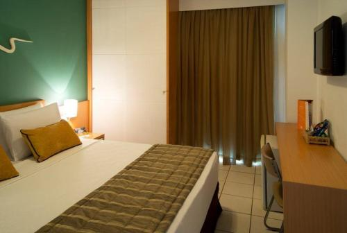 A bed or beds in a room at Praia do Canto Apart Hotel
