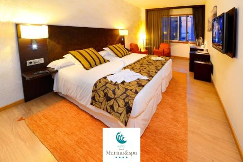 A bed or beds in a room at Hotel Norat Marina & Spa 4* Superior