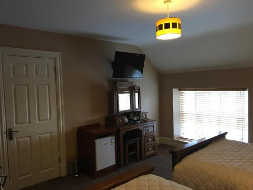 A television and/or entertainment center at Hopper Inn Guest Accommodation