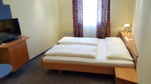 A bed or beds in a room at CenterCourt Hotel