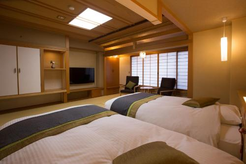 A bed or beds in a room at Matsudaya Hotel
