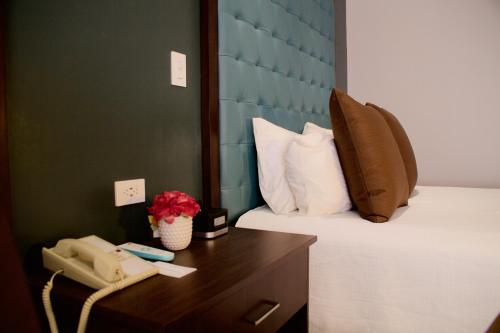 A bed or beds in a room at Munras Inn