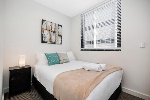 A bed or beds in a room at Astra Apartments Newcastle