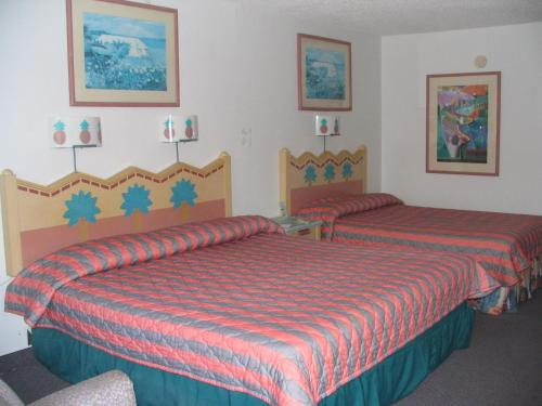 A bed or beds in a room at Ambassador Inn