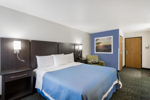A bed or beds in a room at Days Inn & Suites by Wyndham East Flagstaff