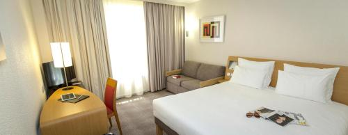 A bed or beds in a room at Novotel Perpignan
