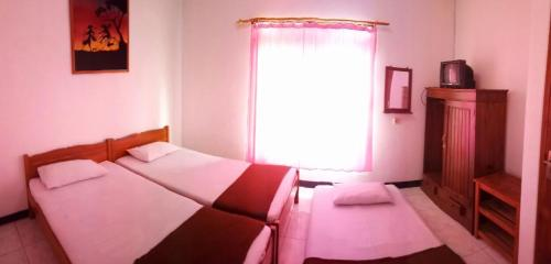 A bed or beds in a room at Rinjani Homestay