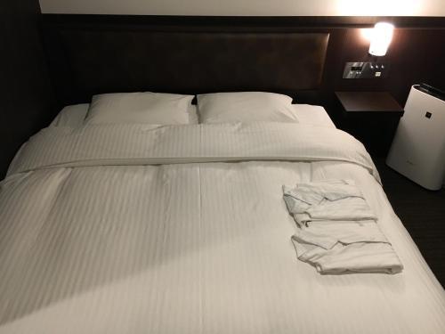 Een bed of bedden in een kamer bij Belken Hotel Tokyo