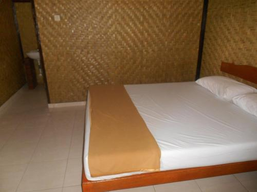 A bed or beds in a room at The Local Menjangan Homestay