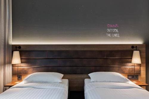 A bed or beds in a room at MOXY Frankfurt East