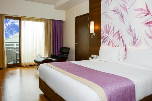 A bed or beds in a room at Purple Palms Resort & Spa