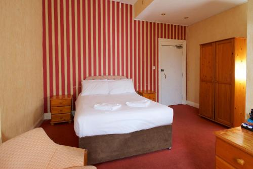 A bed or beds in a room at Glendevon Hotel
