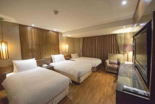 A bed or beds in a room at LeaLea Garden Hotels - Taipei
