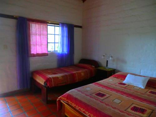 A bed or beds in a room at Le Rendez-Vous Hostal Guesthouse