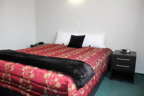 A bed or beds in a room at ASURE Ambassador Motor Lodge