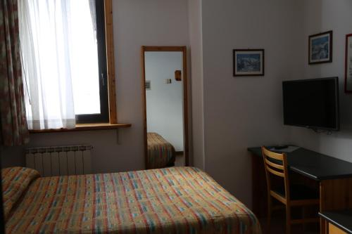 A bed or beds in a room at Hotel Dolomiti
