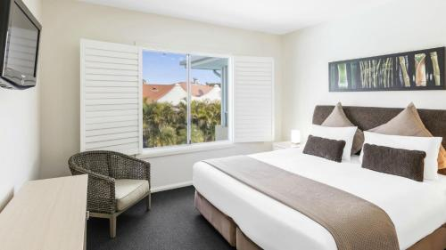 A bed or beds in a room at Oaks Port Stephens Pacific Blue Resort