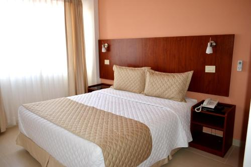 A bed or beds in a room at Premium Suites Business Aparthotel Equipetrol