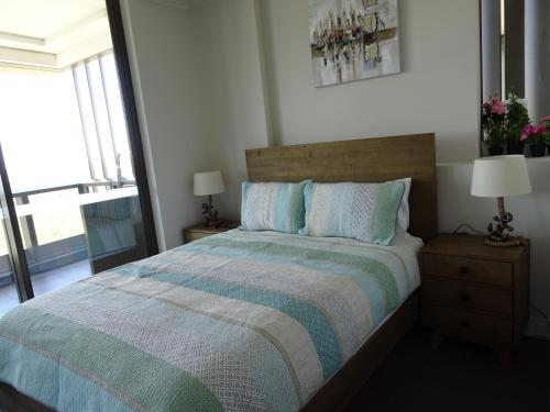 A bed or beds in a room at Sydney Olympic Park Apartment
