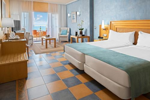 A bed or beds in a room at Elba Sara Beach & Golf Resort