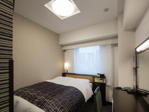 A bed or beds in a room at APA Hotel Kanda Ekimae
