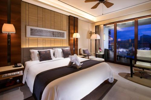 A bed or beds in a room at Holiday Sanya City Center