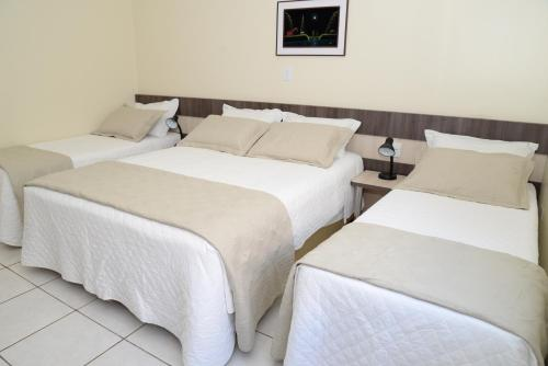 A bed or beds in a room at Palace Hotel Guaíra