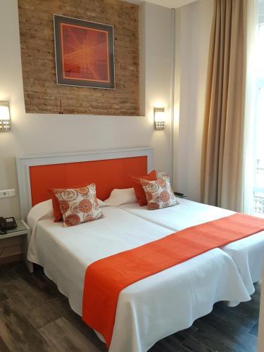 A bed or beds in a room at Hotel y Apartamentos Doña Lola